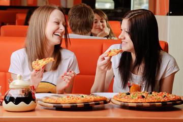 Beautiful young women eating pizza and having fun