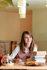 Female Student in pizzeria with books