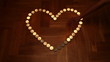 Heart shaped from candles. People light candles.