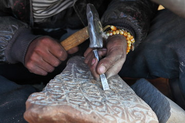 Making Tibetan Buddhist Mani Stone - stone with holy mantras