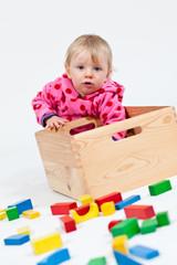 Kind spielt mit Holzbausteine