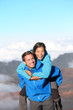 Hiking couple piggybacking happy