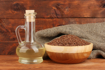 linseed oil with flax seeds on wooden background close-up