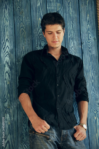 Handsome man casually leaning against the wooden board wall