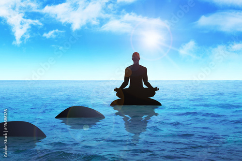 Silhouette of a man figure meditating on a stone