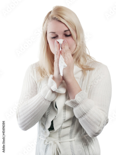 Blond young woman blows her nose - isolated