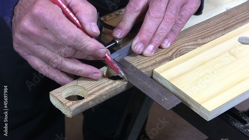 Man drawing a line and cutting a piece of wood with a saw