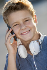 Close up portrait of boy talking on phone outdoors.