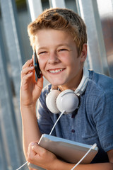 Portrait of smiling boy talking on smart phone.