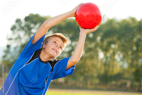 Young boy catching red ball outdoors.