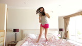 Woman Jumping On Bed And Singing