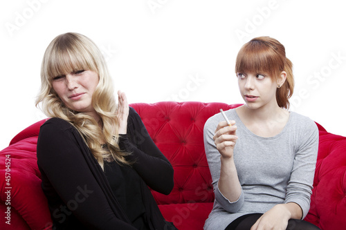 young blond and red haired girls is disgusting of smoke - 45704524