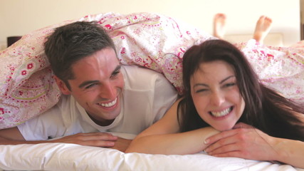 Couple Hiding Under Duvet On Bed