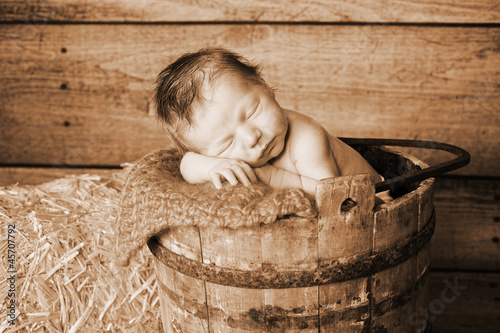 Newborn Baby Boy Sleeping in a Vintage Wooden Bucket