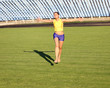 Beautiful teenage sport girl running on the stadium