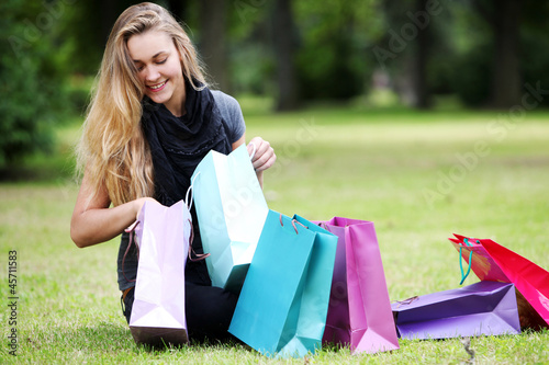 Happy woman with shopping bags in the park