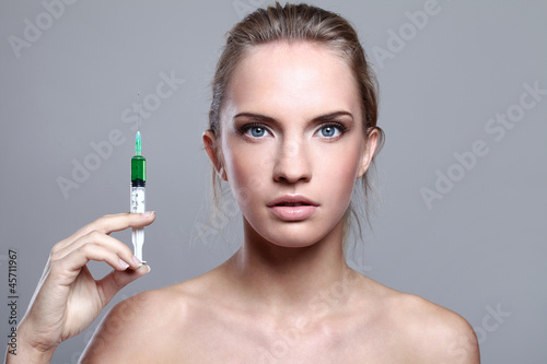 Beautiful woman and syringe with green liquid