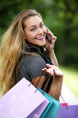 Woman with shopping bags calling by cellphone