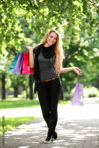 Woman with shopping bags in the park