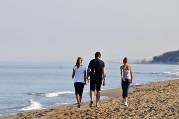 Genitore  e figlie adolescenti camminano sulla spiaggia