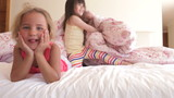 Two Girls Hiding Under Duvet On Bed