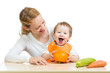 Mother with baby  baby at table. Boy holding pumpkin