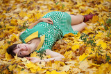 girl lies in maple leaves