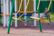 Empty chain swings on summer kids playground