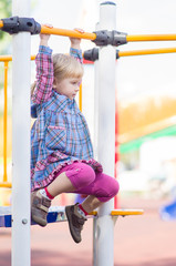 Adorbale girl in dress climbing and crawling on play constructio