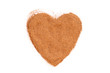 Heap of ground Cinnamon isolated in heart shape on white backgro