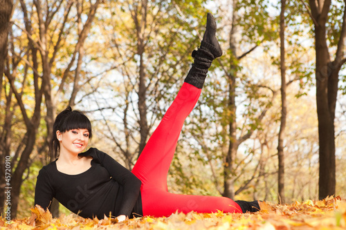 Pretty woman doing sport exercises in the autumn park