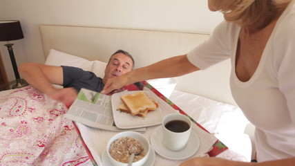 Senior Woman Bringing Husband Breakfast In Bed