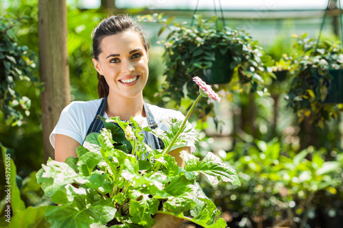 happy young woman with flowers in nursery