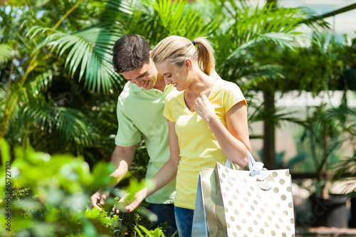 happy young couple shopping for plant in nursery greenhouse