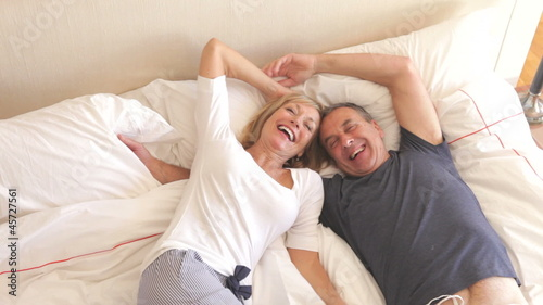 Senior Couple Jumping Onto Bed Together