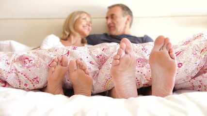 Close Up Of Senior Couple's Feet In Bed