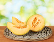 cut melon on wicker mat on green background close-up