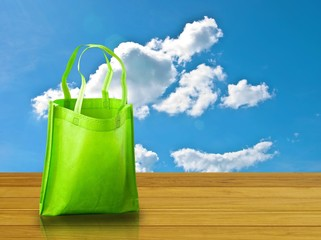 Shopping bag on wooden table with nice sky