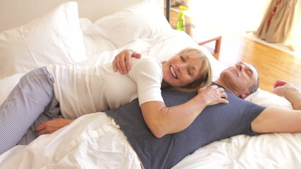 Senior Couple Relaxing In Bed Together