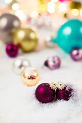 Bonbonfarbene Christbaumkugeln im Schnee