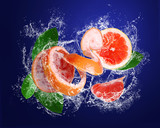 Grapefruit  and pieces with leaves in water splashes