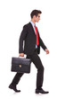 serious business man holding a briefcase and walking