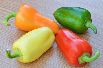 fresh yellow, red, green and orange bell peppers isolated on woo