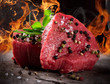 Raw beef steaks with fire flames