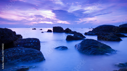 Landscape of sea with dramatic wave and rock in sunset.