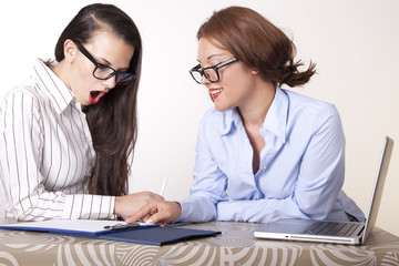 Two young beautiful female secretaries at work