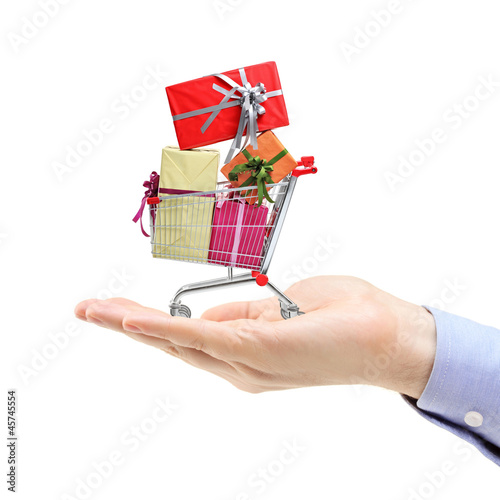 Hand holding a shopping cart full of gift boxes