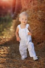 in a field near a haystack funny kid in blue suit