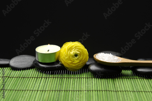 ranunculus ,stones with herbal salt in spoon on green mat