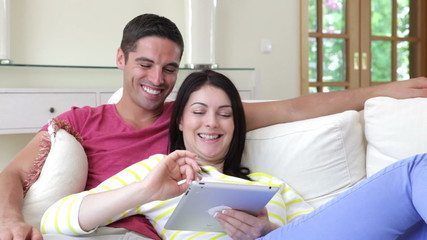 Couple Sitting On Sofa Using Digital Tablet